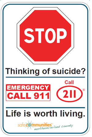 "Railway suicide prevention sign which shoes  a large stop sign and the words ""Thinking of suicide? Call 911, Call 211. Life is worth living."