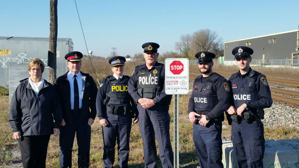 Image of police standing in front of suicide prevention railway sign